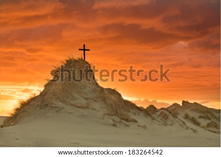 Cross on a tall hill with the sky behind it lit up like gold as the sun goes down.