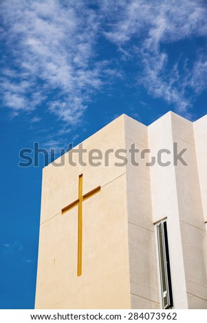 Cross on church over blue sky and clouds - stock photo