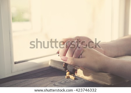 cross on the couple hands on wooden background - stock photo