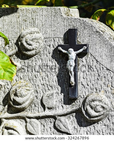 Cross on the tombstone in the public cemetery - stock photo