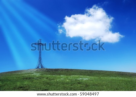 cross on the top of the mountain  illuminated by sunbeams - stock photo