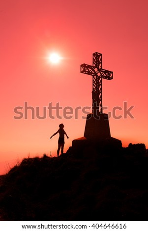 Cross on top of a mountain with open arms woman 
