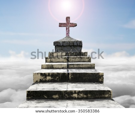 Cross on top of old concrete stairs, with sun sky cloudscape background. - stock photo