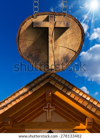 Cross on Tree Trunk with Wooden Church. Wooden Christian cross on a section of tree trunk, hanging from a metal chain. In the background wooden roof of a mountain church - stock photo