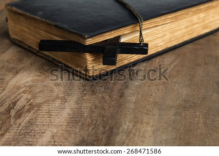 Cross over wood table with old book, holy Bible