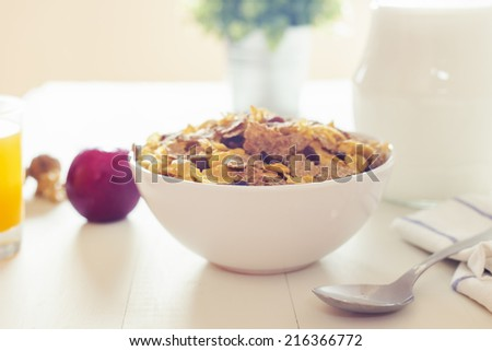 Cross processing style for a delicious breakfast on a white wood table with a belly pitcher of milk, a bowl with cornflakes and raisins, orange juice and opened walnuts. - stock photo