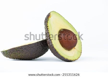 Cross section of avocado fruit on white - stock photo