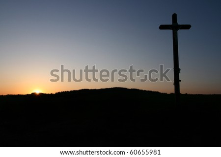 Cross silhouette at sunset - stock photo