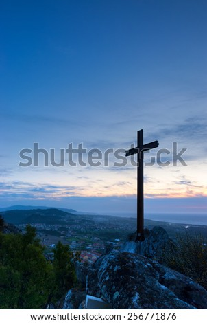 Cross silhouette in the top of a mountain at sunset - stock photo