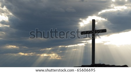 Cross silhouetted against clouds and rays of the sun - stock photo