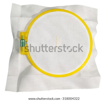 cross-stitch on a white canvas by light orange and white thread on the embroidery frame close-up isolated on white background top view - stock photo