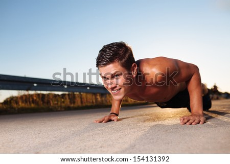 cross-training during sunset. Young man doing push ups. Fitness and health concept - stock photo