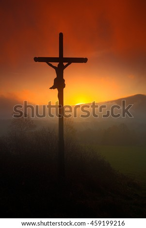 Cross with beautiful sunset with fog. Czech landscape with cross with orange sun and clouds during morning. Hilly mystic landscape with cross. End of night with cross.