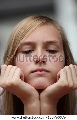 Cross young teenager with her chin resting on her hands, a serious expression and downcast eyes, close up headshot - stock photo