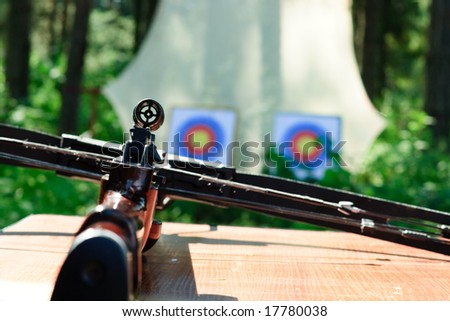Crossbow lying on a table with targets at backgroung - stock photo