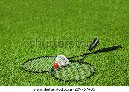 Crossed badminton rackets with shuttlecock over it - stock photo