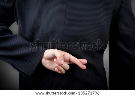Crossed fingers behind the man's back - stock photo