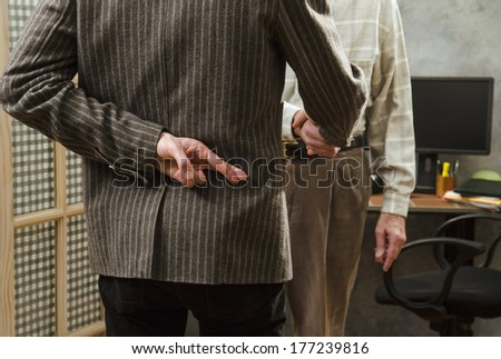crossed fingers while shaking hands - stock photo