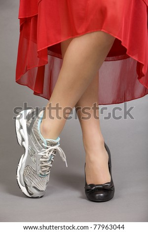 Crossed legs of a beautiful woman wearing and evening gown with one running shoe and one dress shoe - stock photo