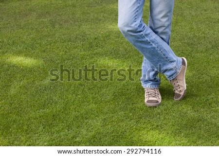 Crossed male legs on green grass field - stock photo