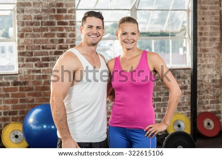 Crossfit couple smilling at the camera in crossfit gym - stock photo