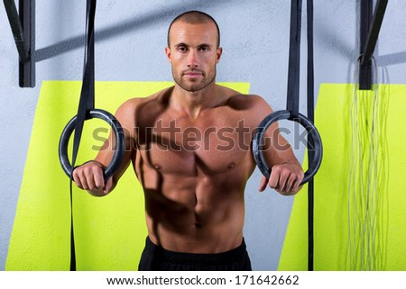 Crossfit dip ring man relaxed after workout at gym dipping exercise - stock photo