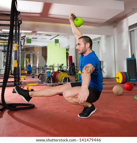 Crossfit fitness man balance Kettlebells with one leg exercise at gym workout - stock photo