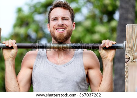 Crossfit fitness man exercising chin-ups workout. Young male adult trainer athlete portrait closeup with hands holding on monkey bars at outdoor gym doing a chin-up strength training muscle exercise. - stock photo