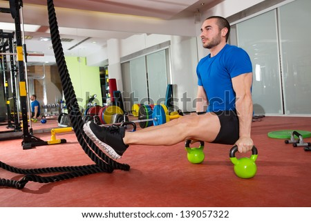Crossfit fitness man L-sits Kettlebells L sits exercise at gym workout - stock photo
