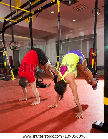 Crossfit fitness TRX training exercises at gym woman and man push-up pushup - stock photo