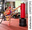 Crossfit fitness woman kick boxing with red punching bag at gym - stock photo