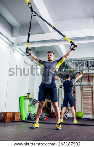 Crossfit instructor at the gym doing TRX Excersise - stock photo