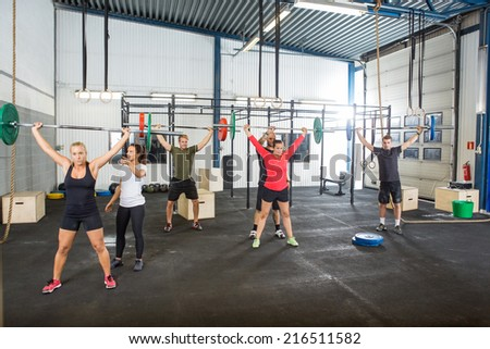 Crossfit instructors assisting athletes in lifting barbells in fitness box - stock photo