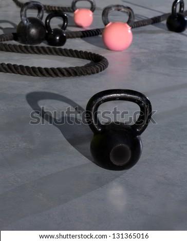Crossfit Kettlebells ropes  in fitness gym floor - stock photo