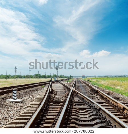 crossing of railroad under blue sky with clouds - stock photo