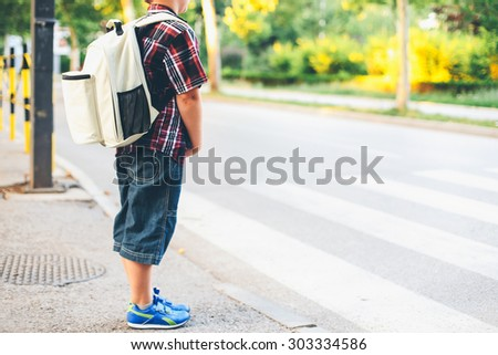 Crossing the street alone. Shallow depth of field - stock photo