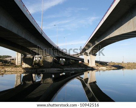 Crossing traffic highway viaducts over the river - stock photo
