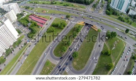 Crossroad traffic at summer cloudy day. Aerial view - stock photo