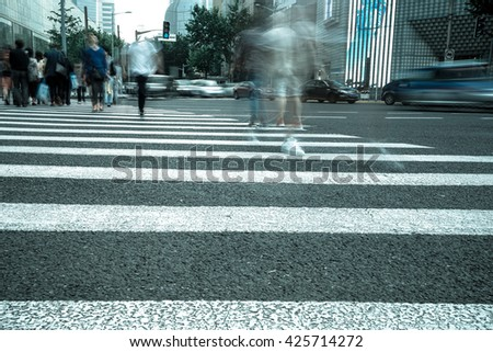 Crosswalk and pedestrian at modern city zebra crossing street in rainy day. Blur abstract. - stock photo