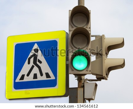 Crosswalk sign and traffic light showing green light for cars