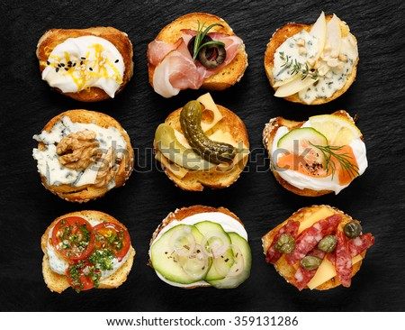 Crostini with different toppings on black background. Delicious appetizers - stock photo