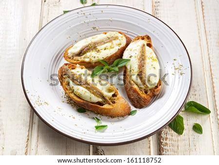 Crostini with fish, mozzarella and oregano - stock photo