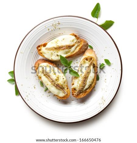 Crostini with fish, mozzarella and oregano on the white background - stock photo