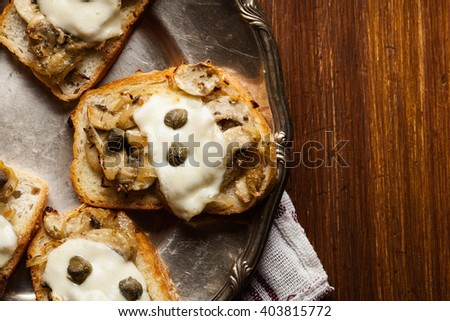 Crostini with fried mushrooms, onion and mozzarella cheese on a plate