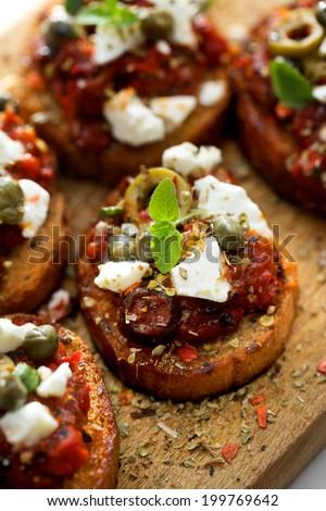 Crostini with roasted tomato salsa,  olives, capers, feta cheese and fresh oregano - stock photo