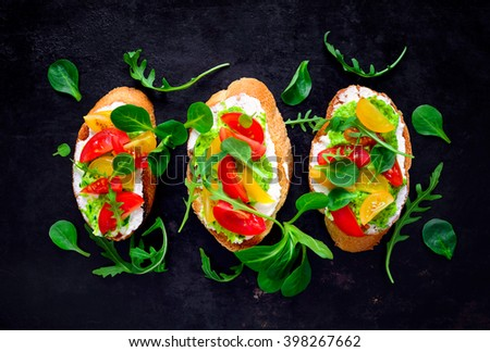 Crostini with whipped feta, pesto, fresh tomatoes and herbs, top view - stock photo