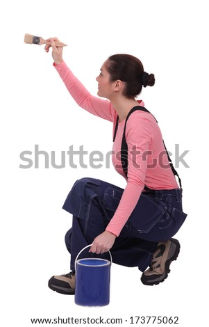 Crouched woman painting wall - stock photo