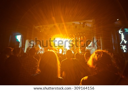 crowd at a concert in orange light noise added - stock photo