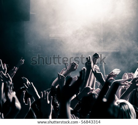 Crowd at a music concert, audience raising hands up, toned - stock photo