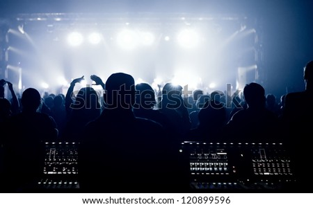 Crowd, cheering and watching a band on stage, with a blue toning - stock photo
